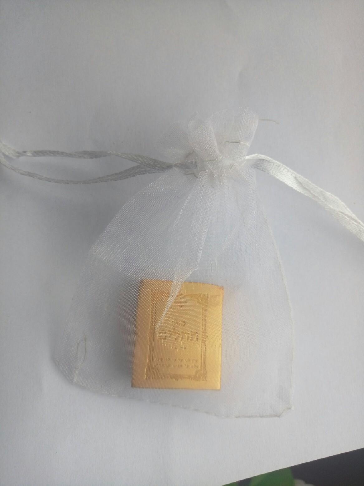 ספר תהילים קטן בצבע זהב בתוך שקית אורגנזה שקופה